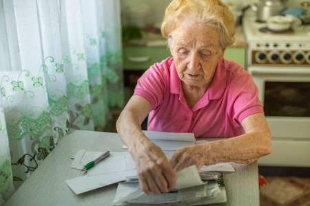 utility payments: An elderly woman fills in for the payment of utilities. Stock Photo