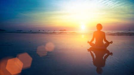 若い女性のシルエットが素晴らしい夕暮れビーチでヨガの練習します。