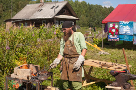 ecovillage: SOGINITSY, RUSSIA - JULY 26, 2014: Unidentified Blacksmith participant during folk festival Ivan-Tea (lat. Chamaenerion) from ecovillage Grishino. Editorial