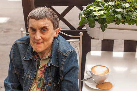 cerebral palsy: Elderly disabled man with cerebral palsy sitting in a street cafe.