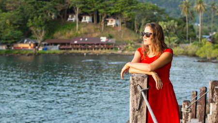 blue lagoon: Spectacular girl in a red dress looks at water of tropical lagoon. Archivio Fotografico
