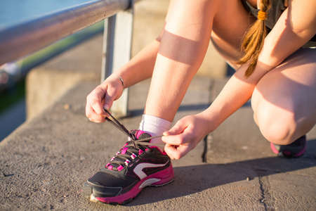 lacing sneakers: Girl tying shoelaces on sneakers. Close-up. Stock Photo