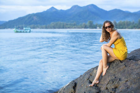stunningly: Stunningly beautiful young woman in a little yellow dress, sits on a stone rock overlooking the Sea in the evening. Stock Photo