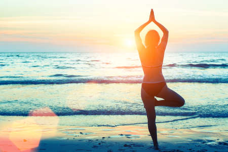 woman pose: Yoga woman silhouette. Woman doing meditation near the ocean. Stock Photo