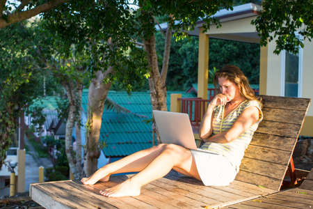 recliner: Girl with laptop sitting on the recliner in the outdoors near the house. Stock Photo