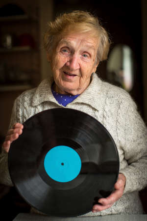 lp: Old grandma with the LP record in hands.