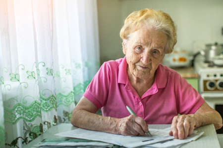 utility payments: An elderly woman fills the bill for payment of utility services. Stock Photo
