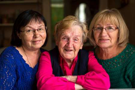 An old woman with two adult daughters. Stockfoto