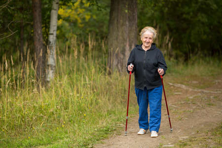 An elderly woman practicing Nordic walking outside of town.