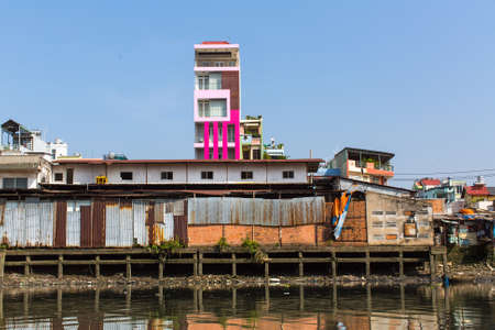 slums: HO CHI MINH, VIETNAM - JAN 11, 2016: Views of the citys Slums from the river. Although the city takes up just 0.6% of the countrys land area, it contains 8.34% of the population of Vietnam. Editorial