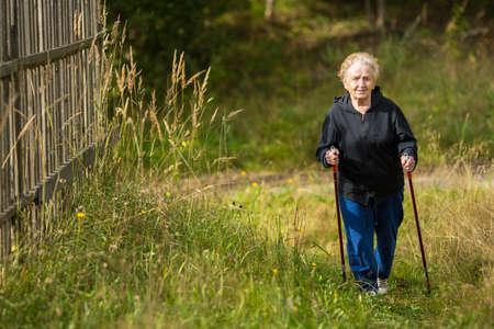 adulto mayor feliz: Una anciana practica la marcha nórdica en el parque.