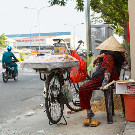 sidewalk sale: HO CHI MINH CITY, VIETNAM - JAN 12, 2016: Unidentified local woman street vendor. Located in the South of Vietnam, is the countrys largest city, population 8 million. Editorial