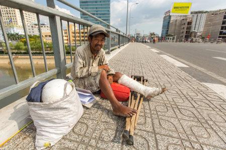 vagabond: HO CHI MINH, VIETNAM - JAN 14, 2016: Unidentified vietnamese beggar sitting on the street. Located in the South of Vietnam, Ho Chi Minh is the countrys largest city, population 8 million.