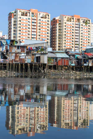 shanty: Views of the citys Slums from the river (in the background and in the water reflection of the new high-rise buildings) Ho Chi Minh City, Vietnam. Stock Photo