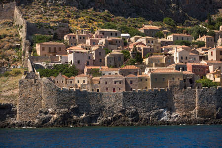 peloponnise: MONEMVASIA, GREECE - CIRCA MAY, 2014: View of stone houses at Medieval fortress. Mainland and the rock on which the city is located, connected by a highway bridge in 1971.