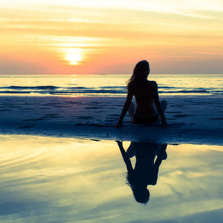 Silhouette girl with long hair on the beach during sunset, with reflection in the water.