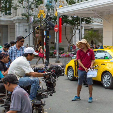 """starring: HO CHI MINH, VIETNAM - JAN 16, 2016: During the filming """"Taxi, whats your name?"""" by vietnamese film director Do Duc Thinh and DOP James Ngo with starring vietnamese movie star Truong Giang. Editorial"""