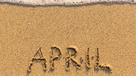 meses del a�o: Inscription APRIL on a gentle beach sand with the soft wave (months of the year series) Foto de archivo
