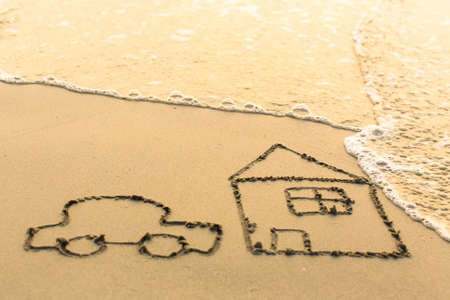 timeshare: House and a Car drawing on the beach sand with the soft wave.