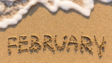 february: Inscription FEBRUARY on a gentle beach sand with the soft wave (months of the year series)