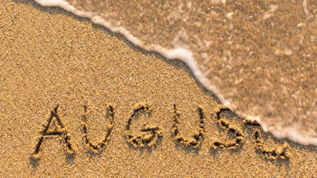months of the year: Inscription AUGUST on a gentle beach sand with the soft wave (months of the year series)