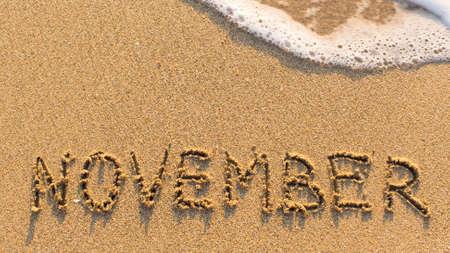 meses del año: La inscripción de noviembre sobre una playa de arena suave con la onda suave (meses de la serie del año) Foto de archivo