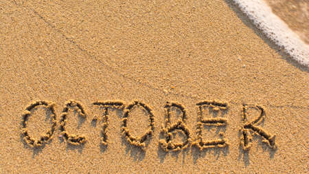 months of the year: Inscription OCTOBER on a gentle beach sand with the soft wave (months of the year series) Stock Photo