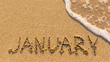 months of the year: Inscription JANUARY on a gentle beach sand with the soft wave (months of the year series)