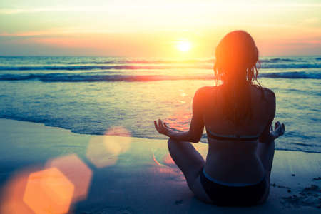 meditation woman: Yoga silhouette. Fitness and healthy lifestyle. Meditation girl on the background of the stunning sea and sunset. Stock Photo