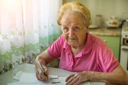 paper people: An elderly woman fills the bill on utility bills.