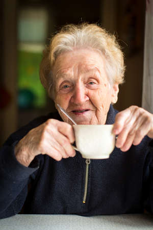 residental care: Old woman drinking tea, portrait close-up.