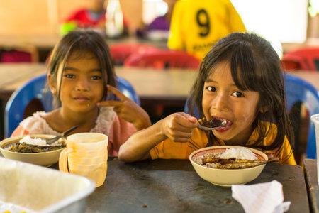 Koh Chang, Thailand - 8 februari 2016: Unidentified kinderen krijgen eten tijdens de lunch op school per project Cambodjaanse Kinder Zorg voor kansarme kinderen in achtergestelde gebieden op Koh Chang eiland te helpen. Redactioneel