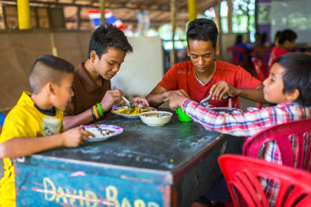 schoolroom: KOH CHANG, THAILAND - FEB 8, 2016: Unidentified children in the classroom at lunch time at school by project Cambodian Kids Care to help deprived children on Koh Chang island.