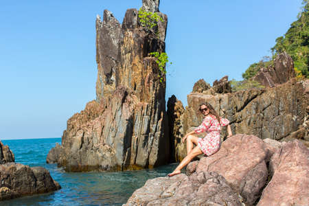 blue sea: Beautiful woman sitting on rocks sea coast.