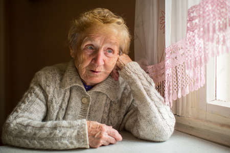 elderly adults: An elderly woman sits in the house near the window.