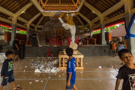 BALI, INDONESIA - FEB 25, 2016: Unidentified local child during built Ogoh-ogoh are statues for the Ngrupuk parade, which takes place on the eve of Nyepi day. Nyepi is a public holiday in Indonesia.