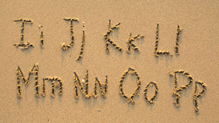 Letters of the alphabet written on sandy beach (from I to P)