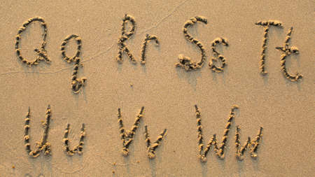 sand drawing: Letters of the alphabet written on sandy beach (from Q to W)