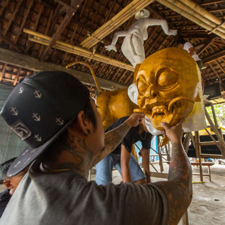 BALI, INDONESIA - FEB 25, 2016: Unidentified local people during built Ogoh-ogoh are statues for the Ngrupuk parade, which takes place on the eve of Nyepi day. Nyepi is a public holiday in Indonesia.
