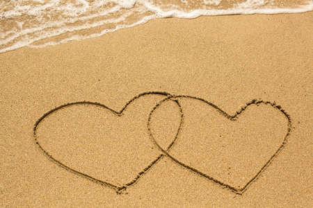Paare von Herzen gezeichnet am Strand Sand am sonnigen Tag