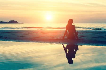 Jonge vrouw zittend op het strand, silhouet bij zonsondergang.