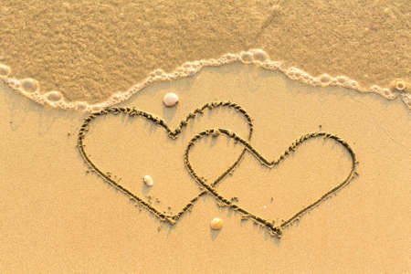 evoking: Two hearts drawn on the sand of a beach. Stock Photo