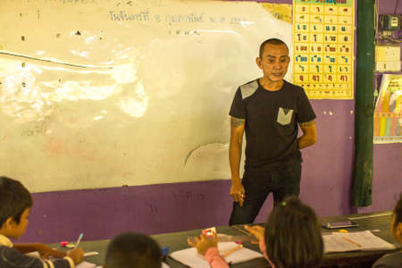deprived: KOH CHANG, THAILAND - FEB 8, 2016: Unidentified ticher in lesson at school by project Cambodian Kids Care to help deprived children in deprived areas with education on Koh Chang island.
