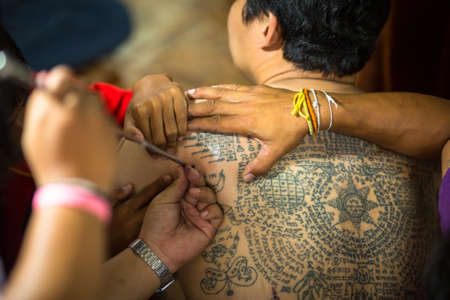 tattooing: WAT BANG PHRA, THAILAND - MART 18, 2016: Unidentified monk makes traditional Yantra tattooing during Wai Kroo Master Day Ceremony in Bang Pra monastery, about 50 km west of Bangkok.