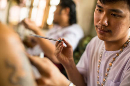 tattooing: WAT BANG PHRA, THAILAND - MAR 18, 2016: Unknown monk makes traditional Yantra tattooing during Wai Kroo Master Day Ceremony in Bang Pra monastery, about 50 km west of Bangkok.