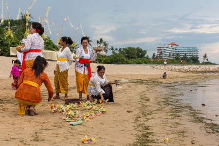 sanur: SANUR, BALI - MAR 18, 2016: Unidentified people during Melasti Ritual. Ceremony is held on the edge of the beach with the aim to purify oneself of all the bad things in the past and throw it to ocean. Editorial