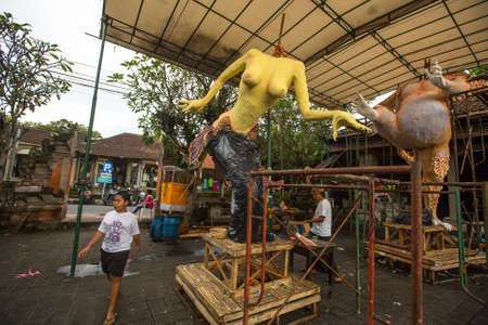 UBUD, INDONESIA - MAR 5, 2016: Unidentified local people during built Ogoh-ogoh are statues for the Ngrupuk parade, which takes place on the eve of Nyepi day. Nyepi is a public holiday in Indonesia.