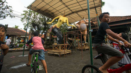 place for children: UBUD, INDONESIA - MAR 5, 2016: Unidentified local children during built Ogoh-ogoh are statues for the Ngrupuk parade, which takes place on eve of Nyepi day. Nyepi is a public holiday in Indonesia. Editorial