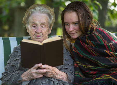Old woman reads a book to her granddaughter, sitting together in the garden. Stock Photo