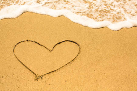 evoking: Heart drawn on the sand of a sea beach. Stock Photo